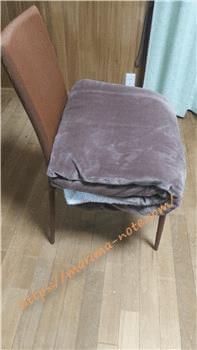 大判ブランケットを畳んで椅子の上に置く