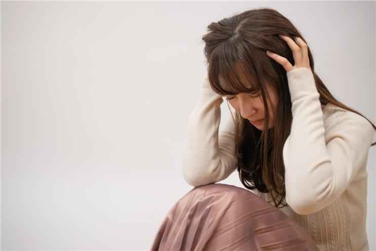 不安に怯えて頭を抱える女性